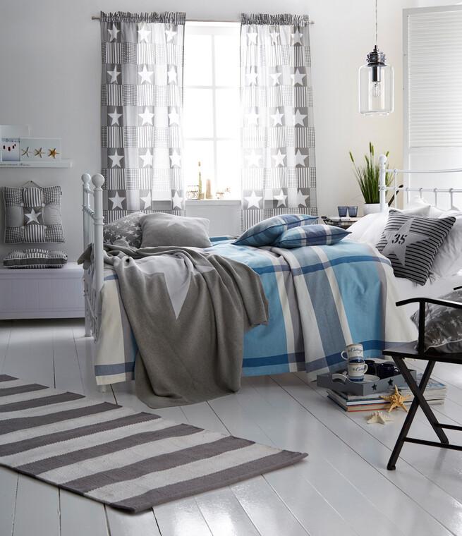 Makuuhuoneen vahva tähtiaiheinen teema pehmeiden värien hillitsemänä