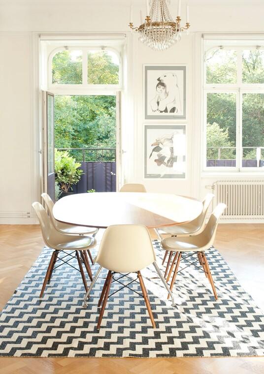 Mustavalkoinen, sahakuvioinen matto kiinnittää katseen ruokailutilan sisustuksessa