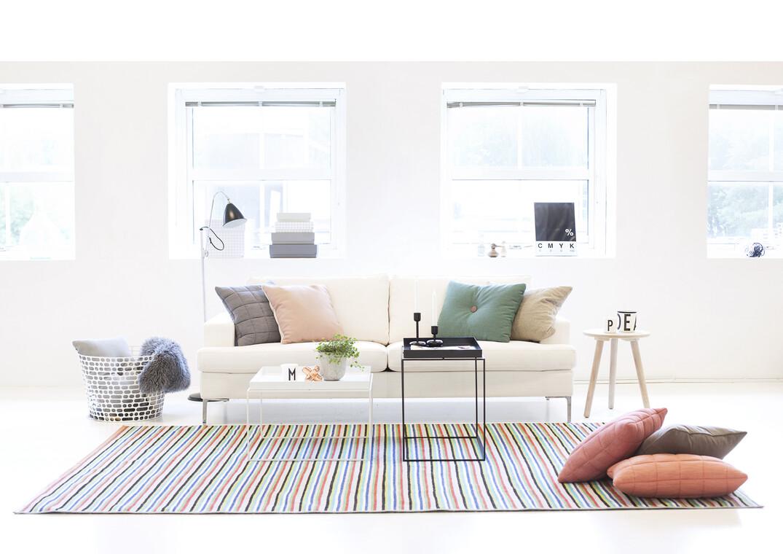 Värikäs harmonia tekstiileillä valkeaan olohuonetilaan