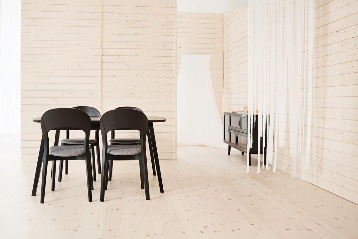 Tummat huonekalut erottuvat edukseen vaaleassa tilassa