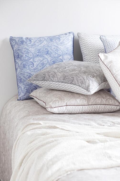 Päiväpeitteen herkkä kuvio toistuu tyynyissä