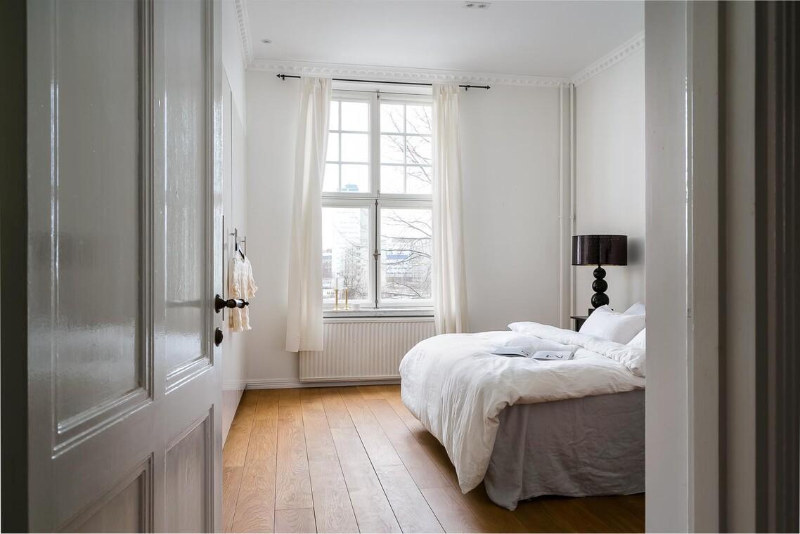 Vanhan puuoven takaa aukeaa kaunis makuuhuone