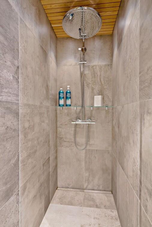 Suuri sadesuihku ja betonimaiset laatat kylpyhuoneessa