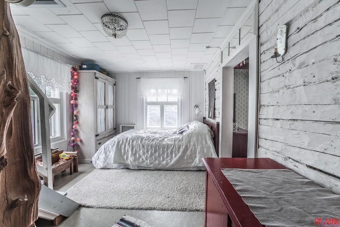 Valkoinen hirsiseinä makuuhuoneessa