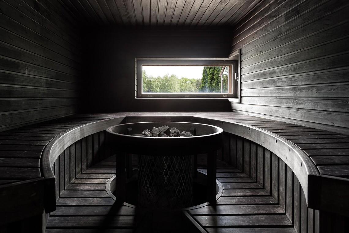 Musta sauna kaarevilla lauteilla