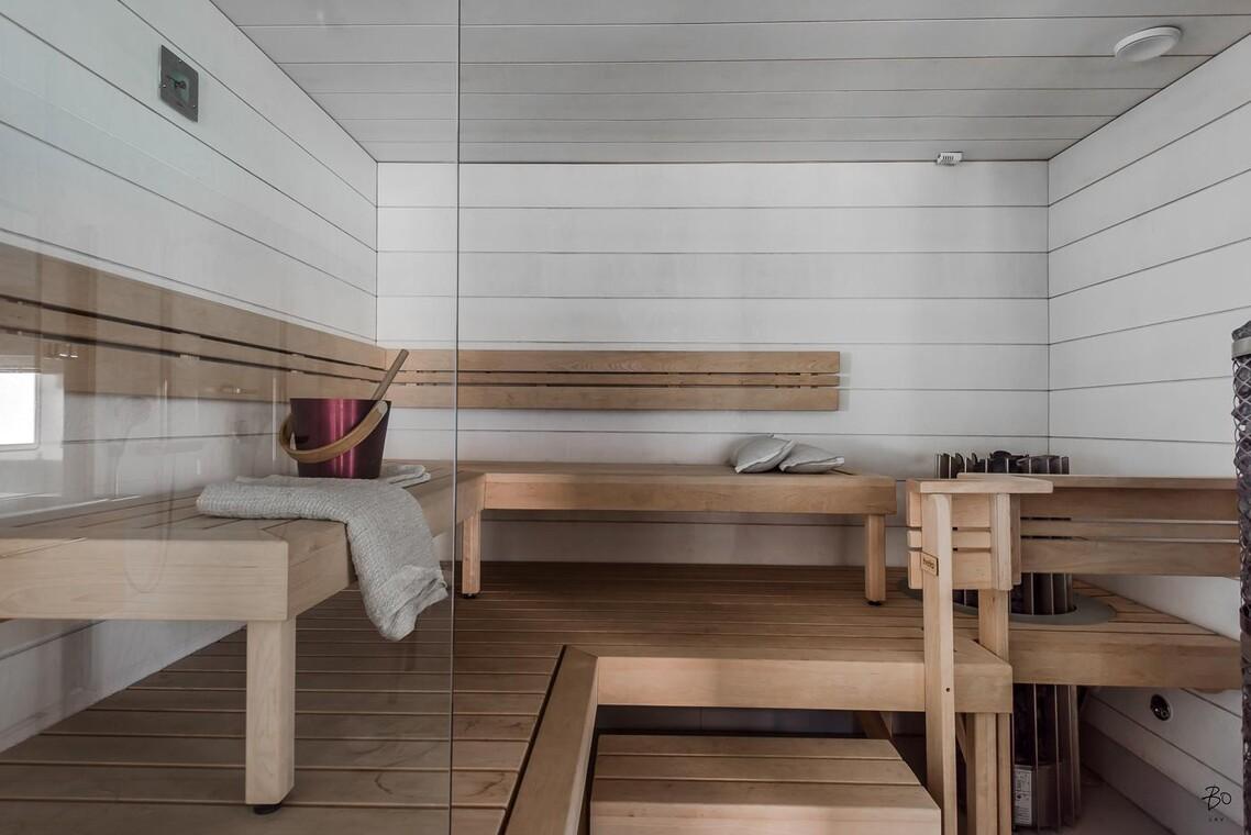 Sauna kahdella kiukaalla ja kuultavan valkoisilla pinnoilla