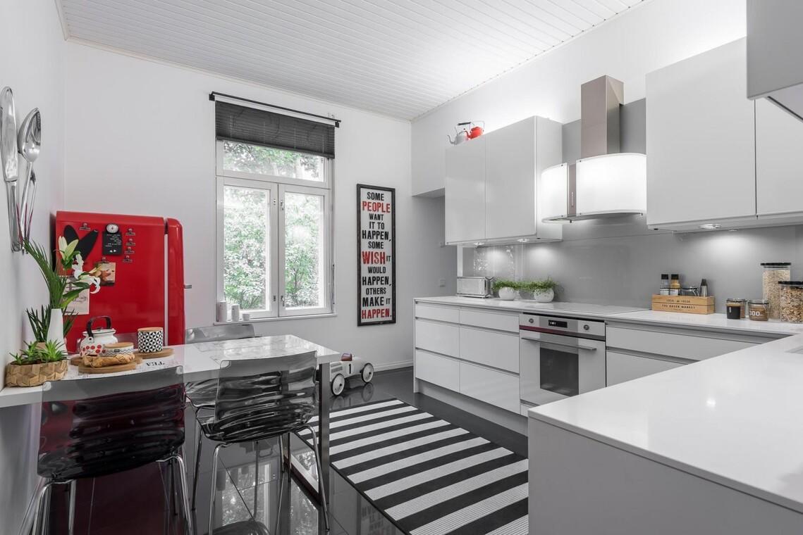 Punainen väripilkku vaaleassa keittiössä