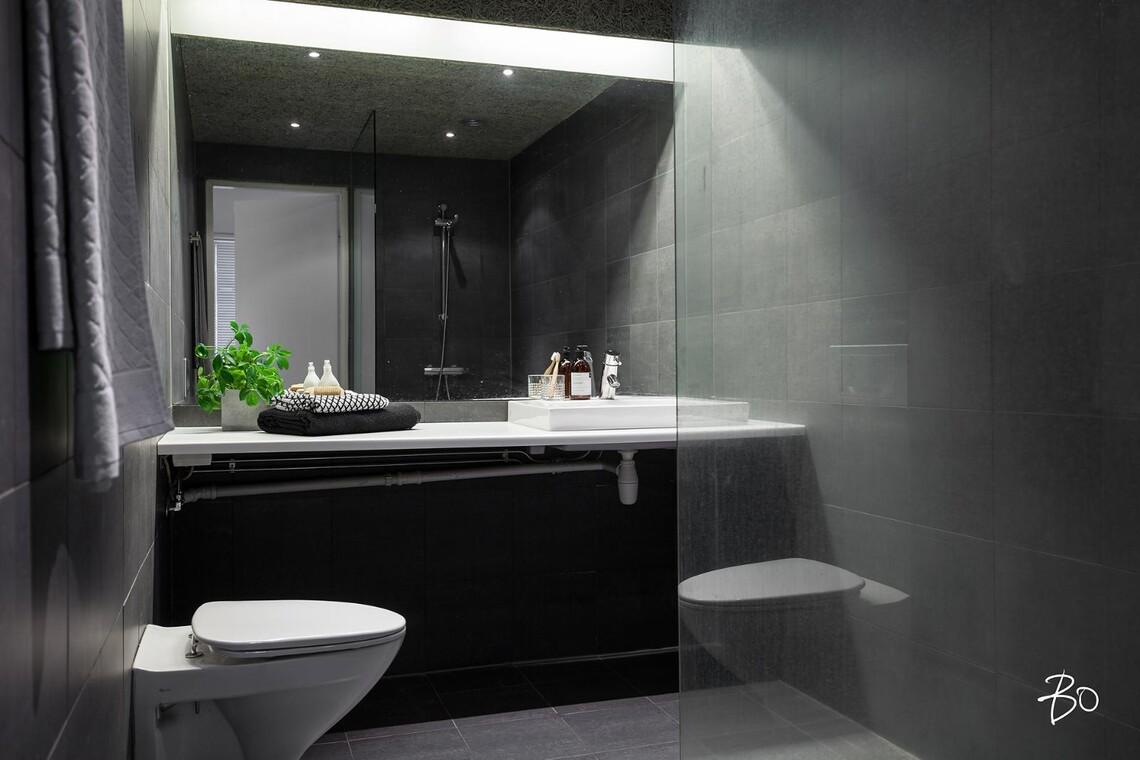 Harmaa kylpyhuone epäsuoralla valaistuksella