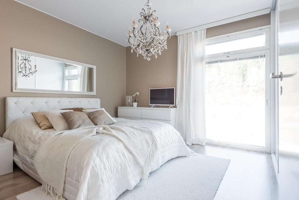 Ylellinen makuuhuone kattokruunuineen