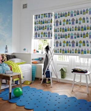 Lastenhuoneen sisustuksen viimeistelee rullakaihtimien värikkäät mökkikuviot