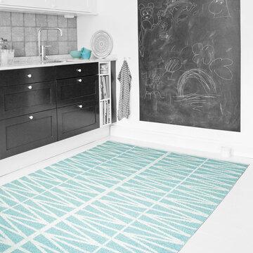 Turkoosisävyinen matto on raikas kontrasti keittiötilan harmaille pinnoille