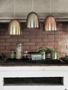 Metallisävyiset valaisimet sopivat keittiön karheisiin seinäpintoihin