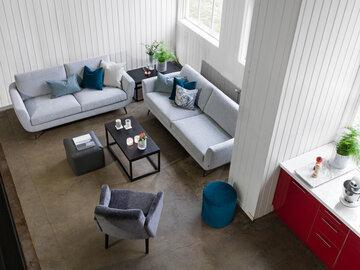 Harmaasävyisen olohuoneen sohvakalusteissa on aavistus retrohenkisyyttä
