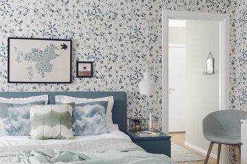Vesivärimäisesti toteutetut kukka-aiheet korostavat sinisävyistä makuuhuonetta