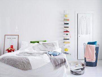 Tekstiilit ja tavarat tuovat väriä makuuhuoneen valkeaan yleisilmeeseen