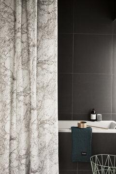 Vivahteikkaan harmaasävyinen suihkuverho harmonisoi kylpyhuoneen sisustuksen