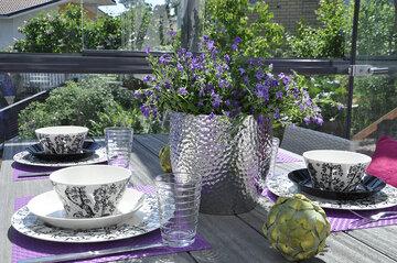 Lasitetulla terassilla nautitaan ruokailuhetkistä auringon lämmittäessä ihanasti