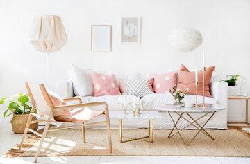 Valoisaa olohuonetta täydentävät hempeät vaaleanpunaiset pastellisävyt ja ihanan muhkea sohva