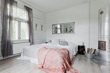 Makuuhuone hirsiseinällä ja pönttöuunilla