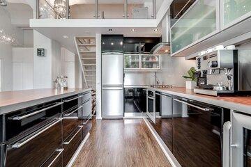 Loft-asunnon moderni musta keittiö