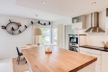 Kiemurteleva kirjahylly keittokirjoille on kuin taideteos keittiön seinällä