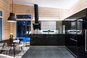 Tyylikäs musta keittiö hirsimökissä