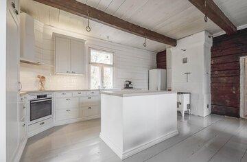 Kattoparruja, lautalattiaa ja hirsiseinää kauniissa keittiössä