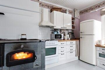 Puuhellan lämpöä keittiössä