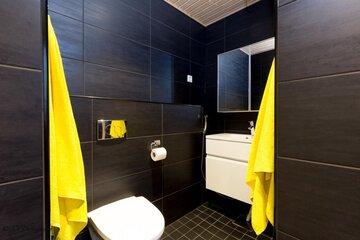 Musta moderni wc ja ripaus keltaista