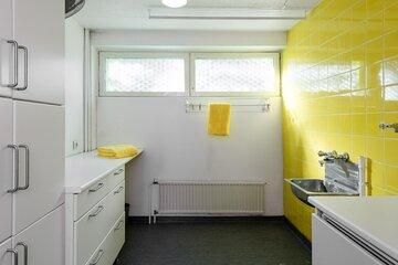 Pirteän keltaiset kaakelit kodinhoitohuoneessa