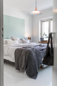 Turkoosi seinään maalattu sängynpääty