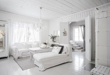 Valkoista maalaisromanttista unelmaa hirsitalon olohuoneessa