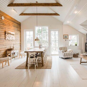 Maalaisromanttinen olohuone kattoparruineen ja hirsiseinineen