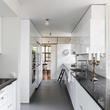 Valkoinen keittiö korkeakiiltokaapeilla
