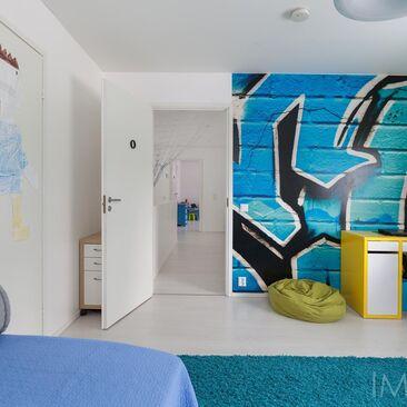 Värikäs graffiti pojan huoneen seinällä