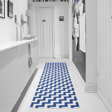 Sinikuvioinen matto piristää harmaasävyisen eteiskäytävän ilmettä