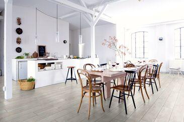 Valkea laminaattilattia korostaa valoisuutta ja kalusteiden muotoa avoimessa ruokailutilassa