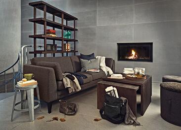 Tummia kangasverhoiltu sohva luo lämmintä tunnelmaa