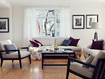 Furninovan sohvalla ja nojatuolilla sisustetussa olohuoneessa on lämmin tunnelma