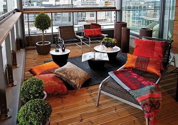 Värikkäät tekstiilit tuovat lämpöä ja tunnelmaa lasitetulle parvekkeelle