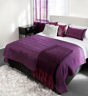Kauniit purppuran väriset tekstiilit tuovat makuuhuoneeseen ylellistä tunnelmaa