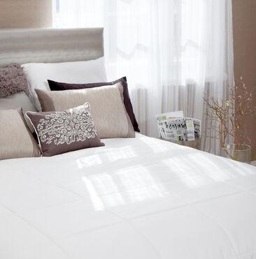 Valo siivilöityy makuuhuoneeseen kauniisti ohuiden verhojen läpi