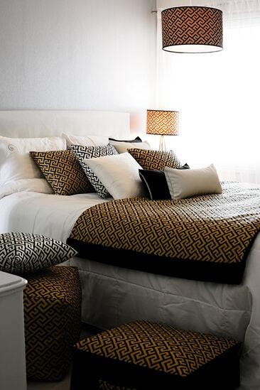 Graafisen kuosin koristamat tekstiilit tuovat makuuhuoneeseen tyylikästä tunnelmaa