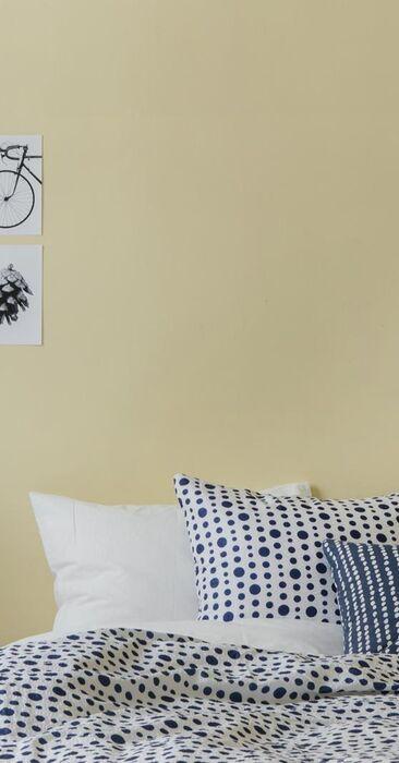 Kaunis keltaisen sävy makuuhuoneen seinässä