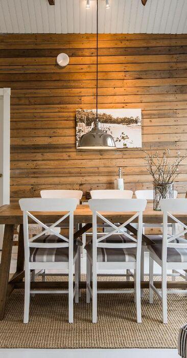Maalaisromanttinen ruokailutila ja kaunis hirsiseinä
