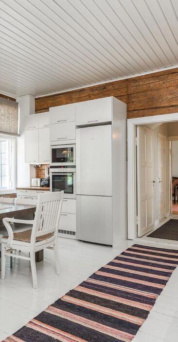 Alkuperäiset hirsiseinät kodikkaassa keittiössä