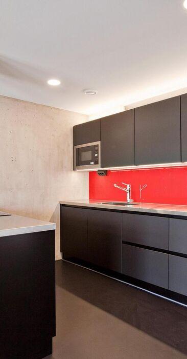 Mustaa, punaista ja betonia loft-kodin keittiössä
