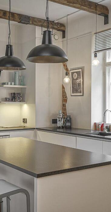 Vanhat kattoparrut ja tiiliseinää modernissa keittiössä
