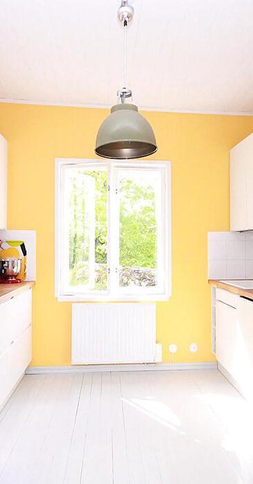 Keltainen keittiö puuhellalla pikkukodissa