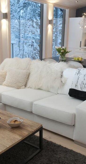 Kaunis valkoinen sisustus hirsihuvilan oleskelutilassa